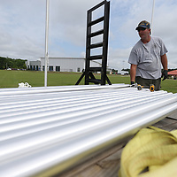Denny Waite gets another 20 ft. flag pole ready to be installed at Veterans Park in Tupelo. The 25 poles are being installed along the road in front of the new Vietnam Memorial Wall in Tupelo.