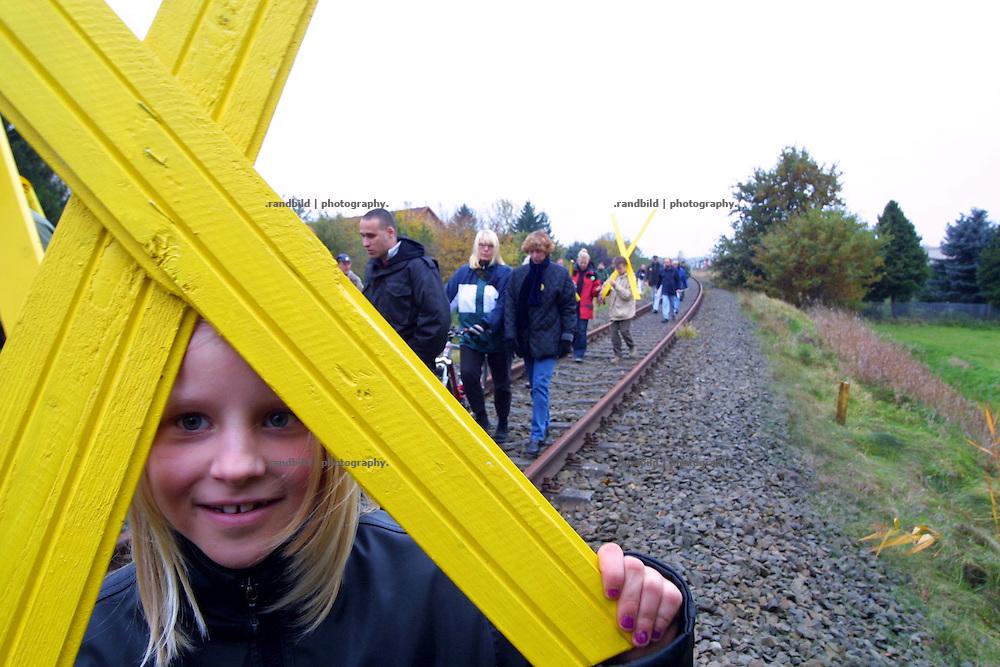 Ein Mädchen hält am Rande einer Anti-Castor-Demonstartion ein gelbes X hoch. Das X ist das Widerstandssymbol gegen die Castortransporte.