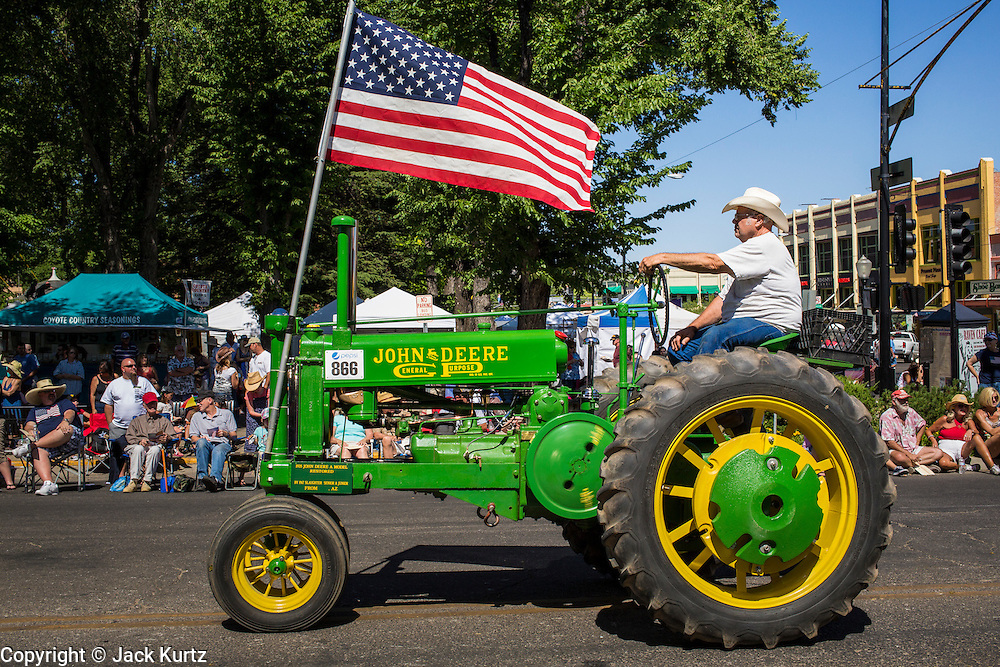 30 JUNE 2012 - PRESCOTT, AZ:   A man drives a 1935 John Deere Model A Tractor in the Prescott Frontier Days Rodeo Parade. The parade is marking its 125th year. It is one of the largest 4th of July Parades in Arizona. Prescott, about 100 miles north of Phoenix, was the first territorial capital of Arizona.   PHOTO BY JACK KURTZ