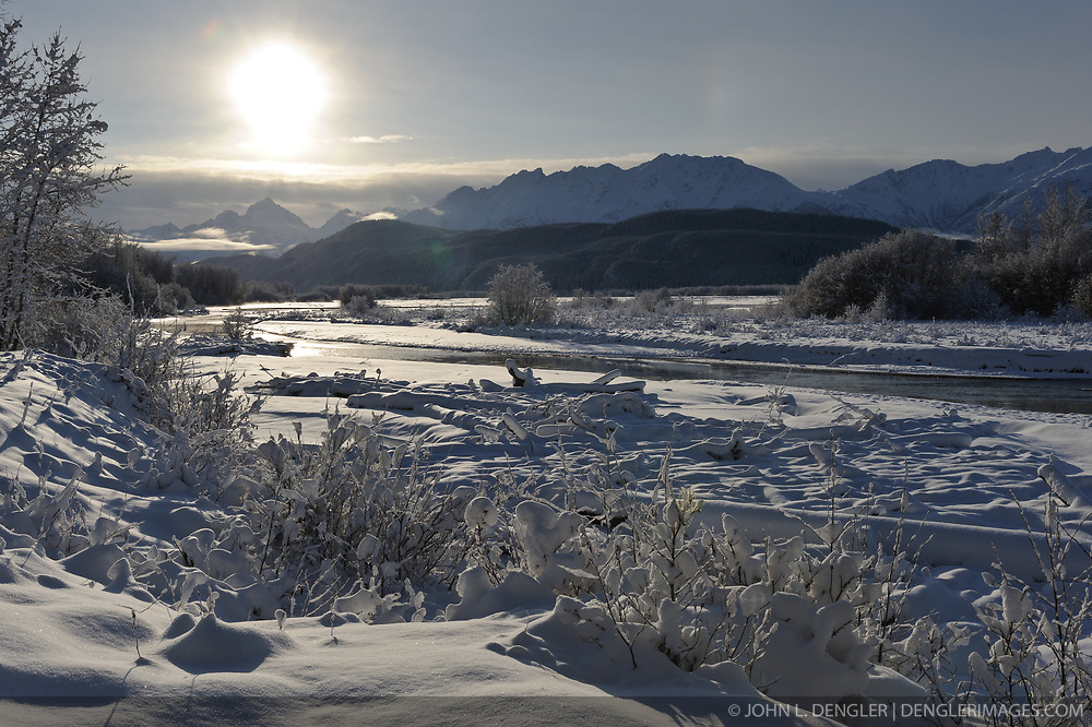 The sun envelopes the Chilkat River following a snowstorm in the Alaska Chilkat Bald Eagle Preserve near Haines, Alaska. One of the largest gatherings of bald eagles in the world occurs in November along the Chilkat River. In 1982, the 48,000 acre area was designated as the Alaska Chilkat Bald Eagle Preserve. In the background are the mountains that make up Takhin Ridge.