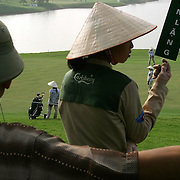 """A course attendant holds a sign saying """"quiet,"""" as local spectators watch a round of golf at Chi Linh Country Club, Hai Duong Province, Vietnam."""