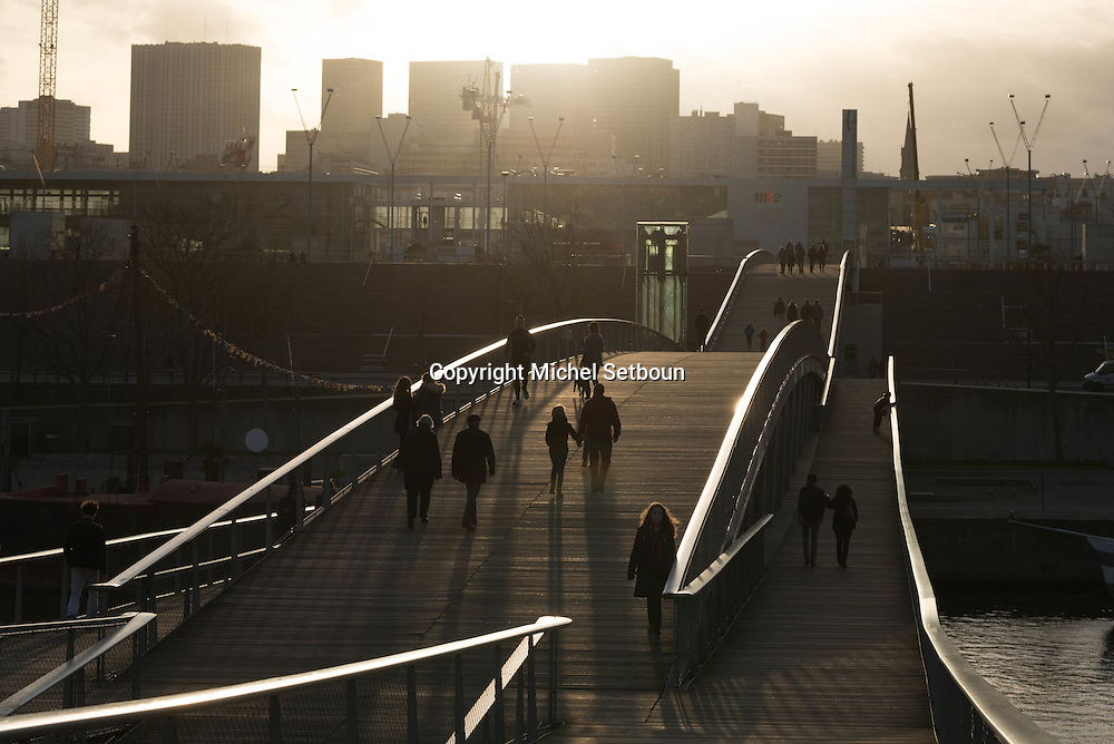 France. Paris, 13th district. Pedestrians on Simone de Beauvoir overpass  over the Seine River, in the distance the french National library