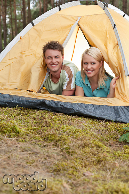 Portrait of happy young couple lying in tent