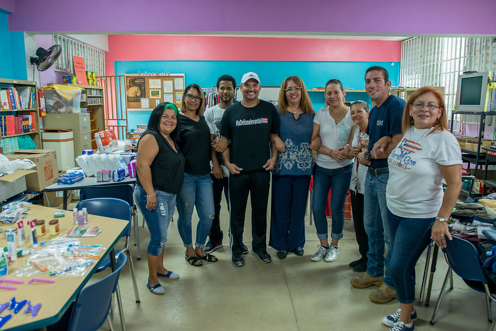 Toa Baja, PR, November 10, 2017-- Teachers and staff of Escuela Delia Cabán in Tao Baja, PR pose for a group shot in the school's library, which served as a distribution point for emergency relief for the Puerto Rico Recovery Fund. The staff worked six days a week distributing water, food, clothes, hygiene sypplies and medicines to their immediate community and to satellite distribution points for nearly two months after Hurriane Maria hit September 20th, 2017. The school opened November 7th, so the library will convert back to being a library Monday, November 14th.  the Puerto Rico Recovery Fund's emergency relief efforts since it was established days after the storm hit September 20, 2017.  Photo by Lori Waselchuk/BRAF