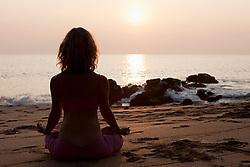 Jul. 25, 2012 - Woman practicing yoga on beach at sunset (Credit Image: © Image Source/ZUMAPRESS.com)