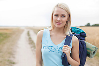 Portrait of beautiful female hiker with backpack standing on field