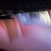 Niagara Falls is illuminated by colored lights at night