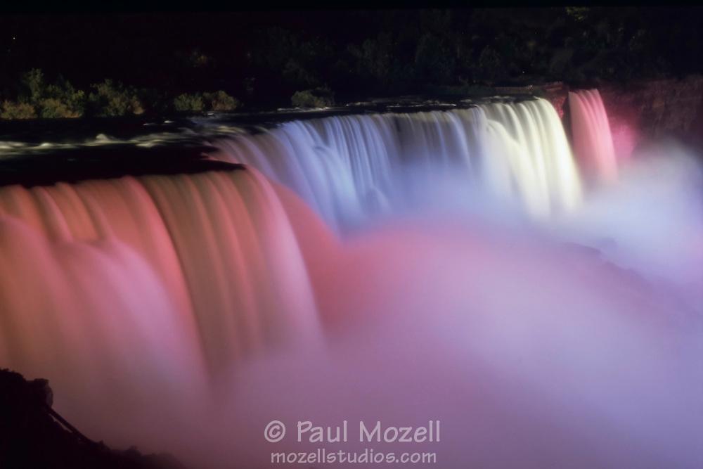 Niagara Falls is illuminated by colored lights at night