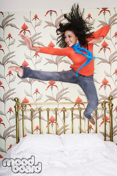 Teenage Girl arms outspread kicking jumping on bed