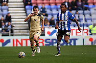 Lewis Cook of Leeds United and Gaetan Bong of Wigan Athletic (r) chase the ball. Skybet football league championship match , Wigan Athletic v Leeds Utd at the DW Stadium in Wigan, Lancs on Saturday 7th March 2014.<br /> pic by Chris Stading, Andrew Orchard sports photography.