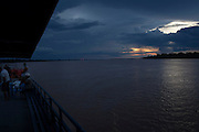 Dramatic skys as another day closes out in the Amazon aboard the Avenger. The Avenger III is a passenger ship making the twice a month journey from the frontier town of Tabatinga in the Três Fronteiras region of Northwestern Brazil, to the capital of the State of Amazonas, Manaus. It's also where the Rio Amazonas enters Brazil from its source in neighboring Peru. <br /> <br /> Carrying passengers and crew totaling almost 200 and small cargo, the ship meanders its way along the Rio Amazonas and Rio Solimoes for four days and three nights. Stopping at half a dozen or so makeshift ports en-route, the service provides a vial link for communities along the river to get products to the city and more importantly, in the absence of roads or airfields, provide a means for the sick to reach care in the city of Manaus.<br /> <br /> For those not fortunate to be accommodated in one of the two or three cabins available, home is space found for a self supplied hammock amongst the kaleidoscopic web of coloured fabrics. <br /> <br /> By the second day, negotiating a stroll from port to starboard can seem more like negotiating an assault course of tangled ropes and personal baggage deliberately piled high to protect ones personal space.<br /> <br /> Food served three times daily is adequate, a staple of soups, chicken, rice and noodles. An 'entertainment' deck on the top floor provides ample opportunity to be social engaging in card and board games with beer swilling, chain smoking locals.