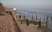 Decaying groynes and sea wall, at Bawdsey manor, Suffolk, England