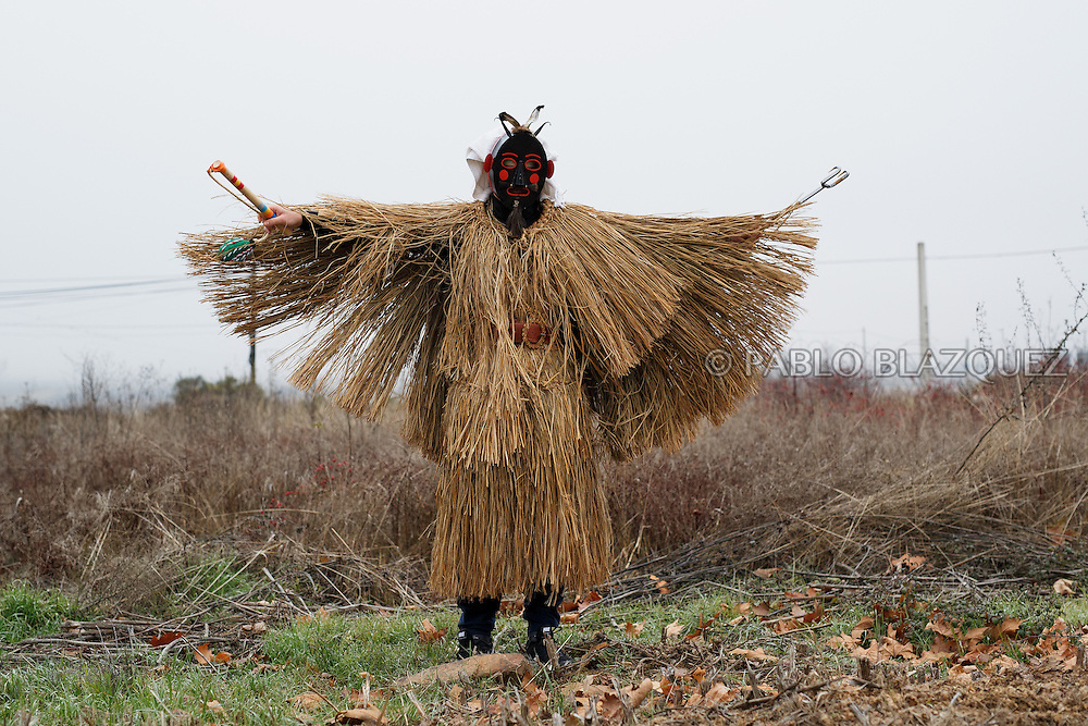 A man dressed as El Tafarron poses for a portrait during El Tafarron festival on December 26, 2016 in Pozuelo de Tabara, Zamora province, Spain.  El tafarron is a pagan winter masquerade that takes place during Saint Esteban festivities. The festival is represented by El Tafarron and La Madama. El wears a custome of straw and a mask. (© Pablo Blazquez)