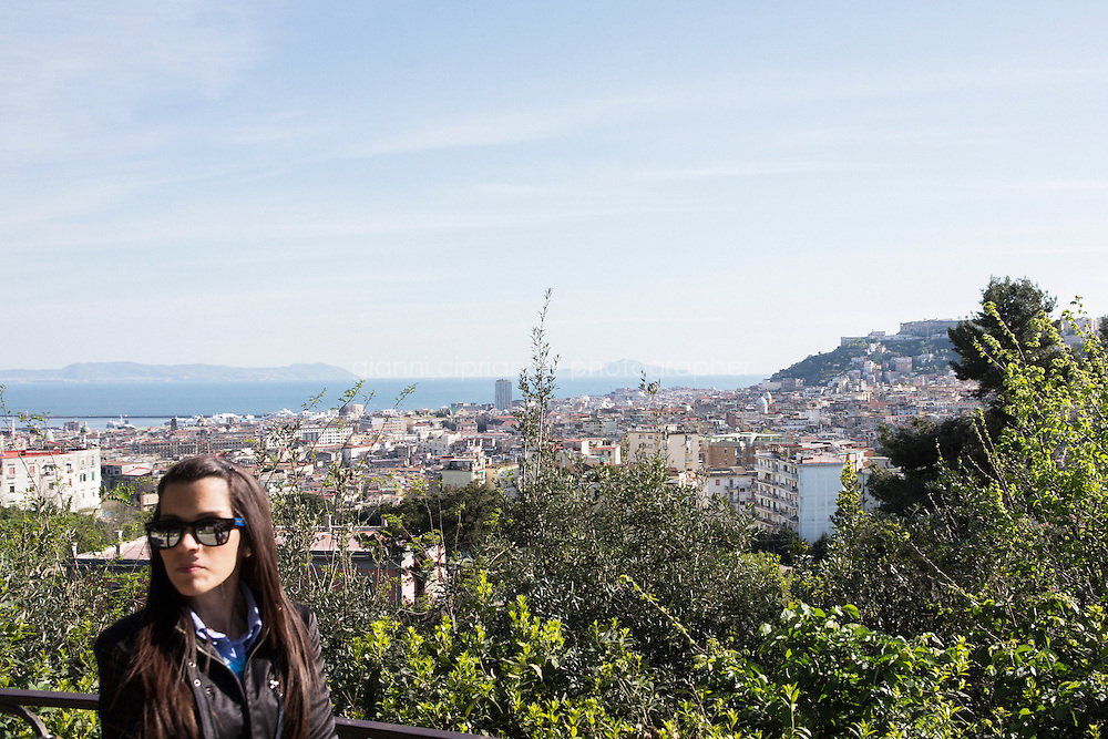NAPLES, ITALY - 10 ARIL 2014:  A woman is here at the panoramic viewpoint of the Capodimonte Park overlooking Naples and the island of Capri (right), in Naples, Italy, on April 10th 2014.