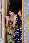 Uzbekistan, Bukhara. Girls waving at the photographer.
