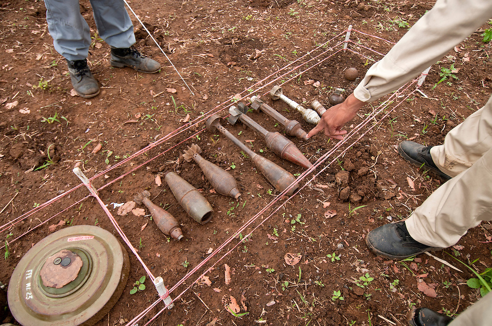 "Sokhon's supervisor, Thor Thoeun, points to examples of land mines and UXO typically found in Cambodia at the MAG base camp at ""Koun Phnum"" or ""Baby Mountain"" minefield...Kheun Sokhon, age 29, is a female deminer for Mines Advisory Group (MAG), in Palin Province, Cambodia.  She searches for land mines - facing the same threat that shattered her life at age 19 - when she stepped on a mine.  She admits, ""I don't want people to experience what I have been through."" .."