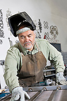 Mature man wearing protective mask working on metal in workshop
