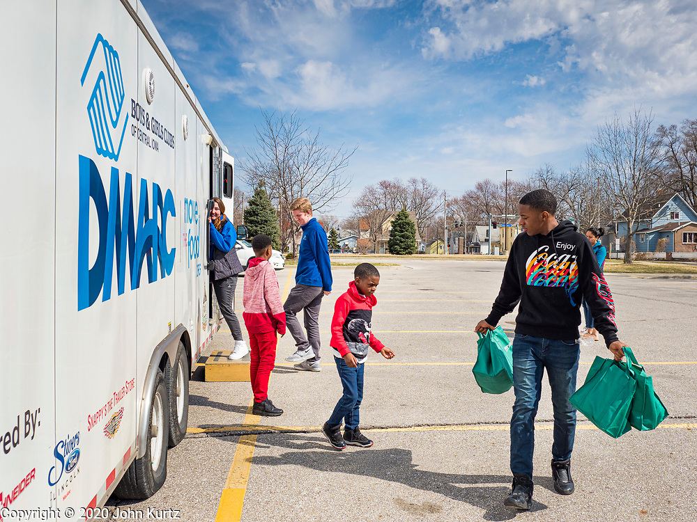 "17 MARCH 2020 - DES MOINES, IOWA: Children walk back to their parents waiting in a car after picking up bags of food in the parking lot of Carver Elementary School in Des Moines. Des Moines Public Schools are closed for at least 30 days because of the Coronavirus outbreak. Des Moines area religious organizations and food banks are working together to bring free food to children in at risk communities. Volunteers and workers are practicing ""social distancing"" by leaving the food packages on the pavement and recipients pick up the packages. Tuesday, the Governor of Iowa ordered all restaurants and bars to close or go to take out only. The Iowa Department of Public Health has urged all public buildings, like libraries and schools, to close, and all schools in Iowa are closed for at least 30 days.     PHOTO BY JACK KURTZ"