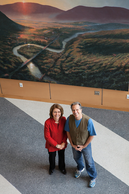 Mass College of Liberal Arts president Mary Grant (R) talks with internationally known artist Steve Hannock, in front of Hannock's painting that hangs in the atrium of the Feigenbaum Center for Science and Innovation, in North Adams on Thursday, October 10, 2013. The long-struggling mill town of North Adams has been revitalized by an infusion of art and artists, encouraged by the state college there and city itself. As a result, hundreds of artists now call it home.  (Matthew Cavanaugh for The Boston Globe)