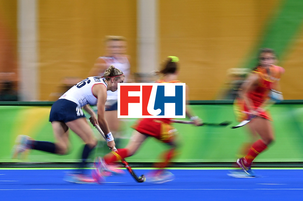 Britain's Lily Owsley (L) runs with the ball to score the third goal of her team during the women's quarterfinal field hockey Britain vs Spain match of the Rio 2016 Olympics Games at the Olympic Hockey Centre in Rio de Janeiro on August 15, 2016. / AFP / MANAN VATSYAYANA        (Photo credit should read MANAN VATSYAYANA/AFP/Getty Images)