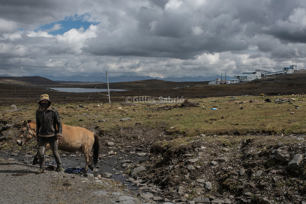 For a story by Ed Wong CHINASICHUAN - Two journals in Sichuan <br /> Tagong, Sichuan, China, October 7th, 2016<br /> A nomad with his horse at a lithium mine near Tagong (Lhagang in Tibetan). In May 2016, mining stopped after villagers protested a leak that polluted the nearby Liqi river killing fishes and yaks downstream. Locals fear the mining might resume as demand for lithium is increasing globally. <br /> Gilles Sabri&eacute; for The New York times