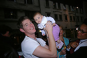 Gavin Burke holding his daughter Lotte.(  His wife Nimmy on right) Party to celebrate Alfred Dunhill at the Goodwood Festival of Speed. Dunhill shop. 48 Jermyn St. London SW1. 9 June 2005. ONE TIME USE ONLY - DO NOT ARCHIVE  © Copyright Photograph by Dafydd Jones 66 Stockwell Park Rd. London SW9 0DA Tel 020 7733 0108 www.dafjones.com