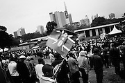 """NAIROBI, KENYA - AUGUST 27, 2011: A young boy waves the Kenyan flag over the crowd at a Kenyans For Kenya gathering in Uhuru Park near downtown Nairobi. Kenyans For Kenya was organized in 2011 as a way for Kenyans to support those suffering from drought and famine in the eastern part of the country.<br /> <br /> Various grassroots initiatives led by youth have begun to improve the quality of life for those living in the direst of conditions, and young people of different tribes are using gardening, waste removal, education and athletics to encourage their peers toward a self-respecting and self-sustaining community. Termed """"youth groups"""" on the street, these initiatives could represent the future of long-term socioeconomic development in Kenya while laying the groundwork for a more peaceful election in 2013. During the post-election violence of 2007 and 2008, impoverished youth in Kenya were routinely bribed by the nation's political elite to carry out acts of violence in their communities. Idleness among the youth, combined with the nation's history of tribal rivalries, were cited as a key factors to the violence, culminating in the deaths of over 1,200 Kenyans and the displacement of over 600,000. Since the violence, many youth have begun to seize active roles in the reform of their nation. In 2010 United States Ambassador Michael Ranneberger said he sensed """"a sea change of attitude"""" among youths, """"a tidal wave below the surface. The youth have woken up."""""""
