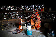 Santosh Devi, aged 19, makes tea in her kitchen. She graduated 2 years ago from the solar engineering course of the Barefoot College in Tilonia, Ajmer, Rajasthan, India. She has since solar powered 20 homes in her village, Balaji Ki Dhani, Bauli, Nagur District, Rajasthan, making it the first village in India to be 100% solar powered in all houses. Above this, she does all maintenance for the neighbouring village, Gudda Ki Dhani, where the previous male solar engineer had left the village to find unrelated work in the city. Barefoot College prefers training women to be solar engineers for this reason that they have higher chances of staying in the village instead of moving to the cities. Photo by Suzanne Lee for Panos London