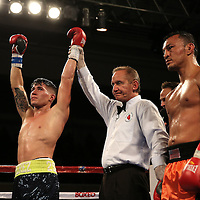 Jovan Perez (L) raises his hands in victory against Juan Aguirre during a Telemundo boxing match at the Kissimmee Civic Center on Friday, July 17, 2015 in Kissimmee, Florida. (AP Photo/Alex Menendez)