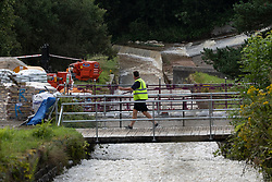 © Licensed to London News Pictures. 03/08/2019. Whaley Bridge, UK. Water pours down Todd Brook as water is pumped out from Toddbrook reservoir and in to the parallel waterway . The town of Whaley Bridge in Derbyshire remains evacuated after heavy rain caused damage to a slipway on the Toddbrook Reservoir , threatening homes and businesses with flooding. Photo credit: Joel Goodman/LNP