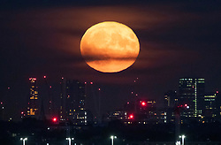 © Licensed to London News Pictures. 14/09/2019. London, UK. The harvest full moon rises over the London Skyline. <br /> September's full moon is also a micro moon because it is furthest from Earth on it's eliptical orbit - appearing 14% smaller. Photo credit: Peter Macdiarmid/LNP