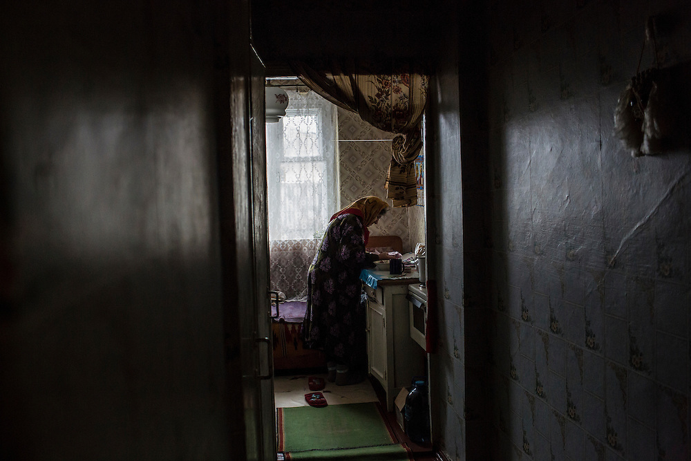 KOMUNAR, UKRAINE - JANUARY 27, 2015: Valentina Mozschagina, 80, who can afford to eat only porridge, searches for medical prescriptions that need to be refilled outside the village at her home in Komunar, Ukraine. Mozschagina is the only caregiver for her disabled son Viktor, 58. CREDIT: Brendan Hoffman for The New York Times