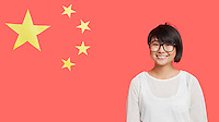 Portrait of happy young woman wearing eyeglasses against Chinese flag