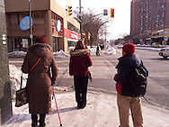 Three people wait to cross the intersection of Ouellette and Wyandotte, heart of downtown Windsor, Ontario.