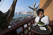 Naha Harbor Diner restaurant on top of an artificial tree. Waitress serving sea grapes.