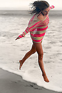 San Diego Fitness Photographer: Girl in Red Stripes leaping at El Matador State Beach in Malibu, CA