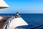 Woman enjoys the ocean view from a yacht deck.