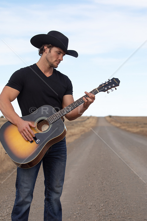 cowboy playing guitar on a rural dirt road