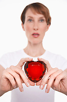 Woman holding heart-shaped jewel between fingers and thumbs