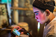"""25 JANUARY 2014 - BANG LUANG, NAKHON PATHOM, THAILAND: A performer with the Sing Tong Teochew opera troupe plays on his smart phone before a show in a Chinese shrine in the town of Bang Luang, Nakhon Pathom, Thailand. The Sing Tong Teochew opera troupe has been together for 60 years and travels through central Thailand and Bangkok performing for mostly ethnic Chinese audiences. Chinese opera was once very popular in Thailand, where it is called """"Ngiew."""" It is usually performed in the Teochew language. Millions of Chinese emigrated to Thailand (then Siam) in the 18th and 19th centuries and brought their cultural practices with them. Recently the popularity of ngiew has faded as people turn to performances of opera on DVD or movies. There are still as many 30 Chinese opera troupes left in Bangkok and its environs. They are especially busy during Chinese New Year when travel from Chinese temple to Chinese temple performing on stages they put up in streets near the temple, sometimes sleeping on hammocks they sling under their stage.     PHOTO BY JACK KURTZ"""