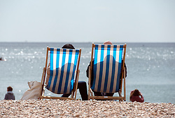 © Licensed to London News Pictures. 18/04/2014. Brighton, UK. People relax in deck chairs on the beach.  People enjoy the  bank holiday sunshine at Brighton today 18th April 2014. Photo credit : Stephen Simpson/LNP