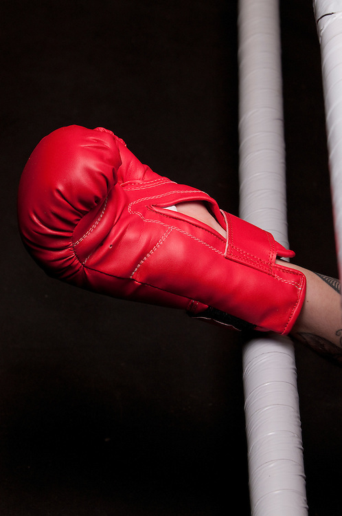 Human hand wearing red boxing glove