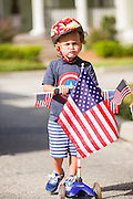 A young boy wearing patriotic costume rides a decorated push scooter during the I'On neighborhood Independence Day parade July 4, 2015 in Mt Pleasant, South Carolina.