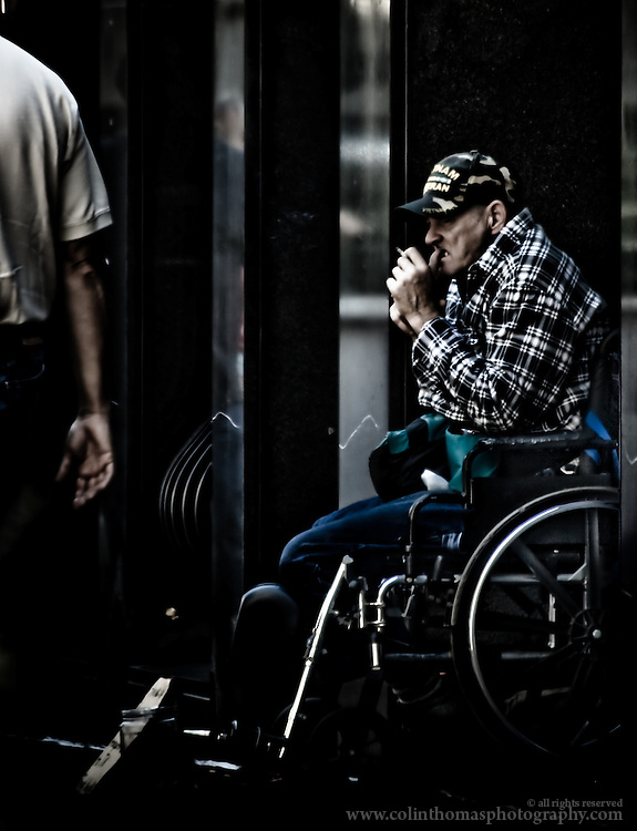Disabled Vietnam veteran sits in a wheelchair and smokes a cigarette on the Downtown Mall in Charlottesville, Virginia.