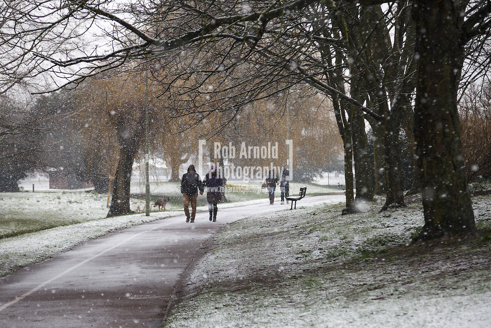 23/03/2013 - Basingstoke, Hampshire, UK. People walking through falling snow in Eastrop Park, Basingstoke. Photo by Rob Arnold