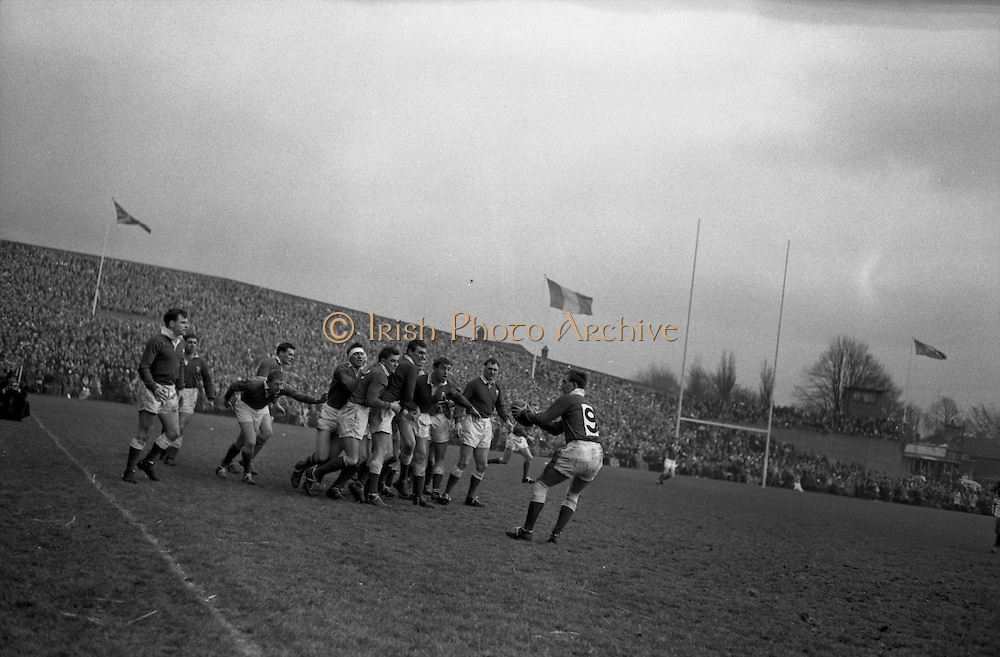 Watkins, Welsh stand off, in loose after line out, passes to his scrum half captain, Rowlands, number 9, ..Irish Rugby Football Union, Ireland v Wales, Five Nations, Landsdowne Road, Dublin, Ireland, Saturday 7th March, 1964,.7.3.1964, 7.3.1964,..Referee- A C Luff, Rugby Football Union, ..Score- Ireland 6 - 15 Wales, ..Irish Team, ..F S Keogh, Wearing  Number 15 Irish jersey, Full Back, Bective Rangers Rugby Football Club, Dublin, Ireland,  ..P J Casey, Wearing number 14 Irish jersey, Right Wing, University College Dublin Rugby Football Club, Dublin, Ireland, .. M K Flynn, Wearing number 13 Irish jersey, Right Centre, Wanderers Rugby Football Club, Dublin, Ireland, ..J C Walsh,  Wearing number 12 Irish jersey, Left Centre, University college Cork Rugby Football Club, Cork, Ireland,..K J Houston, Wearing number 11 Irish jersey, Left Wing, Queens University Rugby Football Club, Belfast, Northern Ireland,..C M H Gibson, Wearing number 10 Irish jersey, Stand Off, Cambridge University Rugby Football Club, Cambridge, England, and, N.I.F.C, Rugby Football Club, Belfast, Northern Ireland, ..J C Kelly, Wearing number 9 Irish jersey, Scrum Half, University College Dublin Rugby Football Club, Dublin, Ireland,..P J Dwyer, Wearing number 1 Irish jersey, Forward, University College Dublin Rugby Football Club, Dublin, Ireland, ..P Lane, Wearing number 2 Irish jersey, Forward, Old Crescent Rugby Football Club, Limerick, Ireland, ..T A Moroney, Wearing number 3 Irish jersey, Forward, University College Dublin Rugby Football Club, Dublin, Ireland, ..W A Mulcahy, Wearing number 4 Irish jersey, Captain of the Irish team, Forward, Bective Rangers Rugby Football Club, Dublin, Ireland,  ..M W Leahy,  Wearing number 5 Irish jersey, Forward, University college Cork Rugby Football Club, Cork, Ireland,..E P McGuire,  Wearing number 6 Irish jersey, Forward, University college Galway Rugby Football Club, Galway, Ireland,..M G Culliton, Wearing number 8 Irish jersey, Forward, Wanderers Rugby Foo