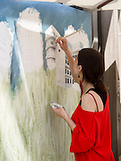 Israel, Tel Aviv, A female artist paints a cityscape of Bauhaus style buildings