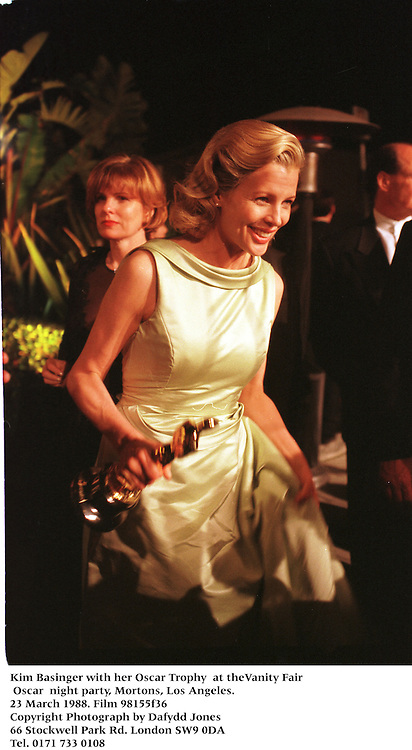 Kim Basinger with her Oscar Tony  at theVanity Fair Oscar  night party, Mortons, Los Angeles. 23 March 1988. Film 98155f36<br /> Copyright Photograph by Dafydd Jones<br /> 66 Stockwell Park Rd. London SW9 0DA<br /> Tel. 0171 733 0108