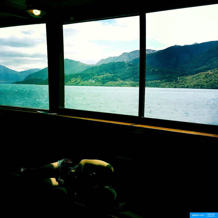A passenger sleeps on the TSS Earnslaw, the 100 year old vintage coal fired passenger steam ship which sails on Lake Wakatipu, Queenstown, New Zealand. The popular tourist attraction is celebrating it's centenary year with celebrations planned for October 2012.  Queenstown, Central Otago, New Zealand. 29th February 2012. Photo Tim Clayton