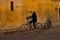 Woman riding a bicycle along Hoi An's waterfront lined with old french colonial architecture.